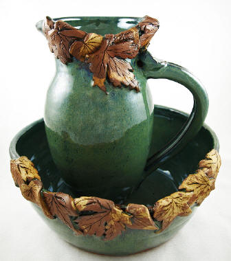Great pottery bowl and pitcher with leafs draped over the edge